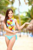 Hawaiian dance - hula dancer vacation concept with beautiful mixed race Asian / Caucasian young woman dancing on tropical beach.
