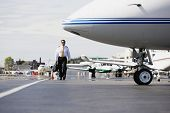 Asian male pilot walking past airplanes on tarmac