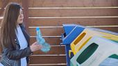 Woman Throwing Garbage Plastic Bottle To Recycling Dumpster poster