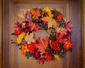 An autumn inspired wreath hanging on an old wooden door. poster