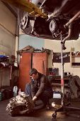 Vertical Shot Of Auto Mechanic Squatting Working On Car Detail On Floor At Auto Repair Shop Under Li poster