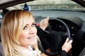Attractive blonde woman driver seated behind the wheel of a right hand drive vehicle looking out of her window with a smile