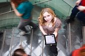At the university/college - Students rushing up and down a busy stairway - confident pretty young female student looking upwards while using her tablet computer(color toned image)
