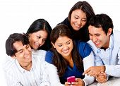 Group of people looking at a cell phone  and smiling - isolated