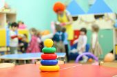Colorful pyramid toy stand at table in kindergarten; children play