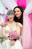 Happy bride stands behind other bride and put hands on her shoulders; Focus on women on right