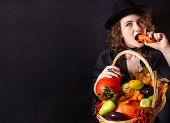 A Girl In A Vampire Costume With Yellow Eyes Holds A Basket With Vegetables. Bright Emotion. Concept poster