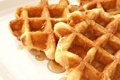 Freshly prepared belgian waffles with maple syrup on cream colored serving plate.  Macro with shallo