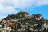 stock photo of saracen  - Monte Tauro with Saracen Castle and Santuario Madonna della Rocca above Taormina in Sicily - JPG