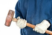 A man wearing old leather gloves holds  a heavy sledgehammer.  Image is isolated for designer convenience.