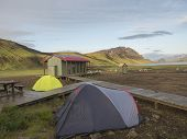 Colorful Tents At Camping Site On Blue Alftavatn Lake With Green Hills And Glacier In The Otherwordl poster
