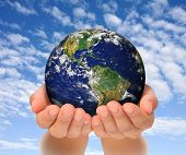 stock photo of take responsibility  - Woman holding globe on her hands South and North America - JPG