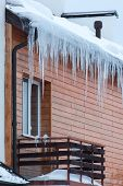 Overhanging Icicles On The House Roof