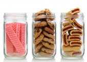 Three glass jars filled with cookies, on a white background with reflection. Jars contain, pink suga