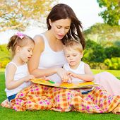 Image of cute young female with two little children read book outdoors, brother and sister with moth