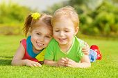 Image of two happy children having fun in the park, brother and sister lying down on green grass, be