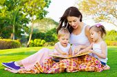 Photo of young brunette woman teaching two sweet kids, cheerful mother with cute daughter and lovely