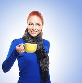 Young woman with the cup of tea over the blue background
