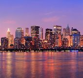 New York City Manhattan downtown skyline at dusk with skyscrapers illuminated over Hudson River pano