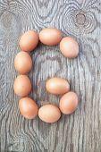 Una letra G de los huevos de Pascua. En una textura de madera.