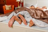 Lovers foot poking out bed covers sleeping couple