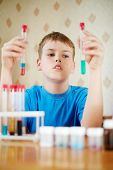 Boy in blue t-shirt sits at table with chemical reagents and looks at two test tubes, which he holds