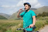 Fit man leaning on his mountain bike drinking water on a trail in the countryside