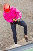 Fit girl abseiling down rock face wearing pink jumper