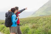 Couple of hikers with backpacks pointing at mountain in the countryside
