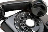 picture of rotary dial telephone  - An old black vintage rotary style telephone off the hook isolated over a white background - JPG