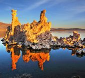 Orange sunset on Mono Lake. Outliers - bizarre limestone calcareous tufa formation reflected in the smooth water.
