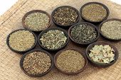 Green herb tea selection in wooden bowls over hessian and wicker background. Selective focus.
