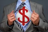 Businessman in classic superman pose tearing his shirt open to reveal a dollar symbol on chest conce