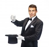 magic, performance, circus, show concept - magician in top hat showing trick with imaginary rabbit