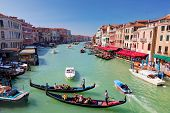 Venice, Italy. Gondola with tourists floats on Grand Canal, Italian Canal Grande among other small s
