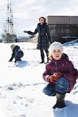stock photo of snowball-fight  - Mother with two children playing a snowball fight next to a sailboat - JPG