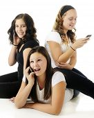 Three young teen friends texting or on the phone.  The one on the floor is acting especially goofy.  On a white background.