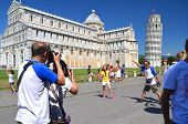 Tourists on Square of Miracles visiting Leaning Tower in Pisa, Italy