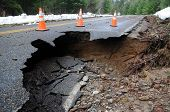 image of paved road  - A sinkhole claims a piece of paved road in the mountains - JPG
