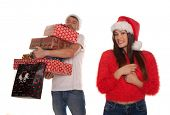 Young couple laden with Christmas presents with the woman standing smiling in the foreground in a festive red Santa Hat while the laughing man holds all the gifts behind her isolated on white