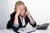 a young woman sitting in office and calling has stress in