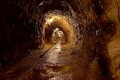 stock photo of catacombs  - Mining tunnel with lights and rails - JPG