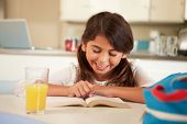 Hispanic Girl With Reading Homework At Table