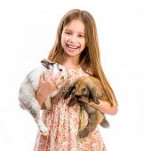 cute smiling girl in a summer dress with two baby rabbits
