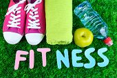 Fitness and healthy life. Conceptual photo. Gumshoes, towel, dumbbells and water bottle on green grass background