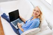 home, technology and internet concept - smiling woman sitting on the couch with laptop computer with