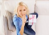holiday, celebration, home and birthday concept - smiling young woman with gift box and making shh g