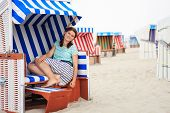 Young Happy Woman Sitting And Relaxing On Beach Chair On The Beach Of Sea.