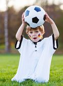 Blond Boy Of 4 Playing Soccer With Football On Football Field