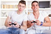 Two Male Friends Playing Video Game With Controllers